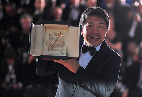 """Japanese director Hirokazu Kore-Eda poses with the trophy on May 19, 2018 during a photocall after he won the Palme d'Or for the film """"Shoplifters (Manbiki Kazoku)"""" at the 71st edition of the Cannes Film Festival in Cannes, southern France.  / AFP PHOTO / LOIC VENANCE"""